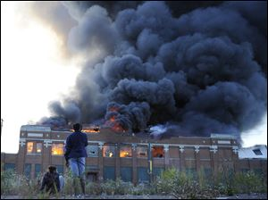 Onlookers watch as a large plume of smoke rises above a warehouse building on Detroit's west side on Sept. 26.