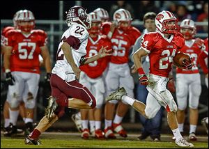 Eastwood's Brent Schlombohm, who had 104 yards rushing, runs past Rossford's Noah Asmus.
