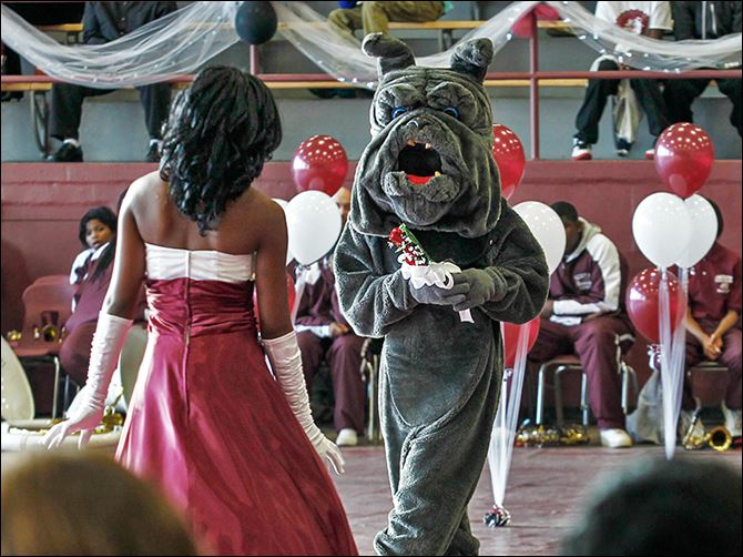 n7scott-8 Brittani Graves of the Class of 2017 is met by her escort, the Bulldog mascot, during the kickoff of Scott High's centennial celebration in the school's field house Friday.
