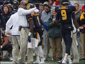University of Toledo head football coach Matt Campbell kisses the helmet of Bernard Reedy after he scored the winning touchdown.