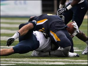 Navy's Cody Peterson yanks back the head of UT's David Fluellen during 2nd half. Fluellen was taken out of the game injured. No penalty called.