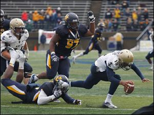 Navy quarterback Keenan Reynolds is tripped up by UT's defense during 2nd half.