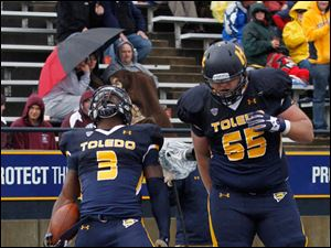 Toledo's Kareem Hunt celebrates scoring a touchdown in the 3rd quarter. 65 is Chase Nelson.