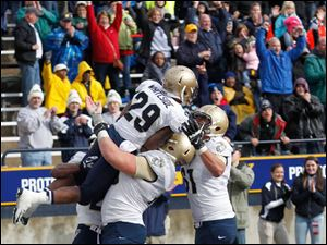 Navy's Geoffrey Whiteside is lifted in the air by Tanner Fleming after scoring a touchdown in the 2nd overtime.