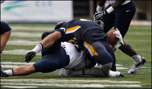 Navy's Cody Peterson yanks back the head of UT's David Fluellen during 2nd half at the University of Toledo Glass Bowl in Toledo, Ohio. Fluellen was taken out of the game injured. No penalty called.