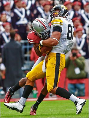 Ohio State cornerback Bradley Roby, left, tackles Iowa tight end C.J. Fiedorwicz with a hard hit in the first quarter. Roby was ejected from the game for a targeting penalty.