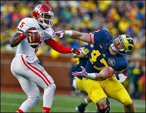 Michigan's Jake Ryan just misses Indiana quarterback Tre Roberson, who threw for 288 yards and ran for 50.