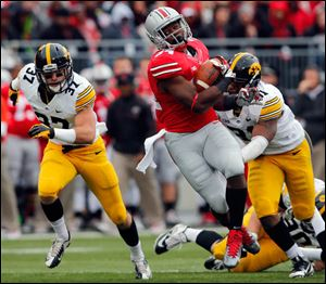 Ohio State TB Carlos Hyde (34) runs the ball against Iowa LB Anthony Hitchens (31) during the second quarter.