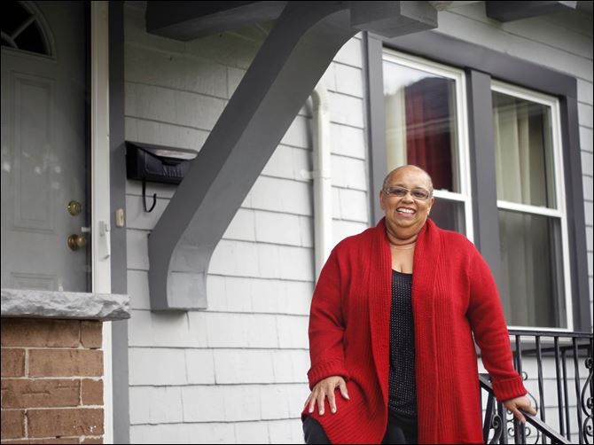 First time buyer Gilda Coleman stands on the porch of her new home.