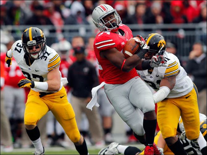SPT osufb20p Ohio State TB Carlos Hyde (34) runs the ball against Iowa LB Anthony Hitchens (31) during the second quarter.