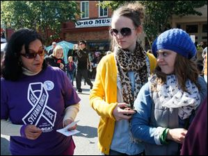 Dr. Maneesha Pandey, left, speaks with Megan Watkins, 14, center, and her sister Amanda Watkins, 19, both of Toledo about the recently formed Sylvania Domestic Violence Task Force.
