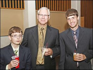 Adoptive family members Bradley, 13, left, and Garry, 18, right, attended this year's Adopt America Network benefit dinner with their father Matt Armstrong at Stranahan Great Hall in South Toledo.