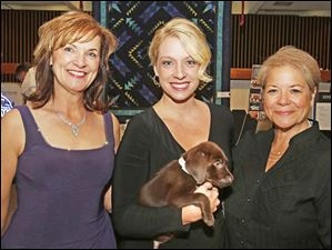 Chairman of the Board of Trustees of Adopt America Sharon Gillespie, left, Jessica Ransom, holding eight-week-old Chocolate Lab Bob, center and President and CEO of Dave Thomas Foundation for Adoption Rita Soronen, right.