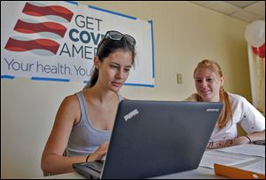 Ashley Hentze, left, of Lakeland, Fla., gets help signing up for Affordable Care Act insurance from Kristen Nash, a volunteer with Enroll America in Tampa.