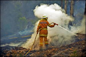 A volunteer firefighter in New South Wales puts out hot spots in the town of Bell, Australia, on Sunday. The blazes are exacerbated by wind and high temperatures.