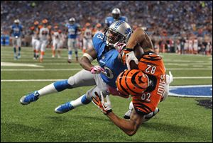 Cincinnati Bengals wide receiver Marvin Jones catches a 12-yard touchdown as Lions cornerback Chris Houston defends in the second quarter Sunday in Detroit.