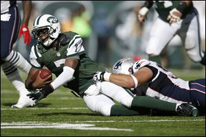 New York Jets quarterback Geno Smith is sacked by New England Patriots lineman Chris Jones on Sunday in East Rutherford, N.J. Jets kicker Nick Folk was wide left on a 56-yarder in overtime, but the miss was negated when Jones, a star at Bowling Green State University, was called for unsportsmanlike conduct for pushing a teammate forward to try to block the kick. It marked the first time that new penalty has been called in an NFL game.