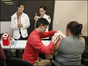 Adam McCabe, a student in the University of Toledo School of Pharmacy, ad-ministers a flu shot to an uninsured woman.