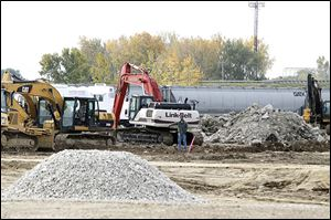 Crews work along the site of the warehouse being built at the $18 million Ironville development in East Toledo.