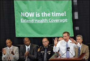 Ohio Gov. John Kasich speaks about health coverage in the Ohio Statehouse in Columbus in July.