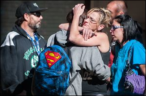 A Sparks Middle School student, back to camera, cries with family members after being released from Agnes Risley Elementary School today in Sparks Nev., after a shooting at Sparks Middle School.