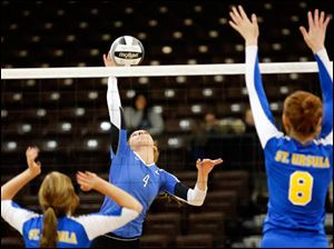 Anthony Wayne's Stephanie Olman (4) spikes the ball against St. Ursula's Lauran Graves (8).