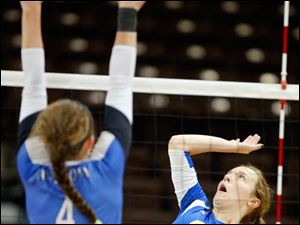 St. Ursula's Emily Lydey (9) hits the ball against   Anthony Wayne's Stephanie Olman (4).