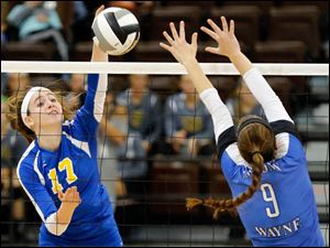 St. Ursula's Morgan Finn (17) spikes the ball against Anthony Wayne's Callie Drage (9).