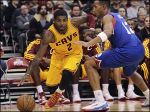 Cleveland Cavaliers' Kyrie Irving, left, drives the baseline against Philadelphia 76ers' Evan Turner during the third quarter.