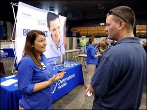 Registered nurse Salanda Bowman, left, talks with part-time Kentucky Wesleyan College student Jason Ward, of Whitesville, about job openings at the Owensboro Health Regional Hospital during a Regional Career and Job Fair in the Owensboro Sports Center  in Owensboro, Ky. earlier this month.