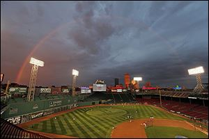 Boston Red Sox players take batting practice as a rainbow appears in the sky above Fenway Park Tuesday, Oct. 22, 2013, in Boston.