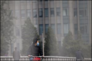 A woman wearing a face mask looks at the traffic as she bicycles on a road in Beijing today.
