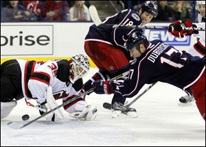 Columbus Blue Jackets' Brandon Dubinsky, right, scores against New Jersey Devils goalie Cory Schneider during the second period.