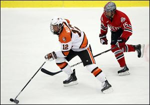 Bowling Green State University's Bryce Williamson (12) moves the puck against  against Ohio State's Nick Oddo (15)  during a hockey game Oct. 15, 2013, in Bowling Green, Ohio.