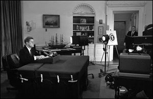 U.S. President John F. Kennedy addresses the nation by television and radio from the Oval Office in Washington, announcing a U.S. naval blockade of Cuba.