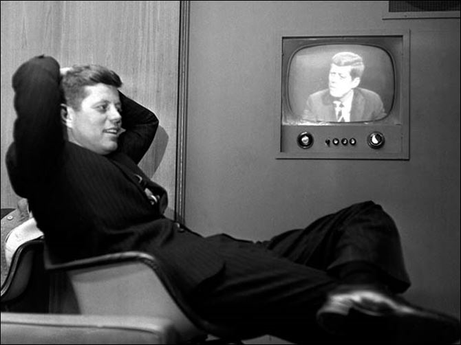 In this April 3, 1960 file photo, Sen.  In this April 3, 1960 file photo, Sen. John F. Kennedy, Democratic presidential nominee, sits next to a playback of his televised appearance in Milwaukee, Wis. for the Wisconsin presidential primary two days later.