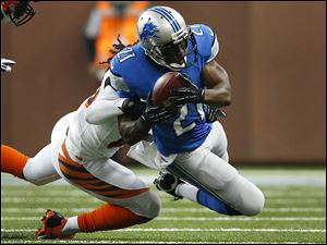 Detroit Lions running back Reggie Bush (21) is brought down by Cincinnati Bengals free safety Reggie Nelson (20) in the first quarter of an NFL football game Sunday, Oct. 20, 2013, in Detroit. (AP Photo/Rick Osentoski)