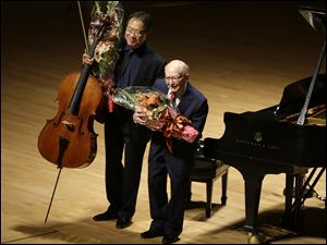 Cellist Yo-Yo Ma, left, and Holocaust survivor George Horner, right, hold flowers as they bow after performing together on stage at Symphony Hall Tuesday, Oct. 22, 2013, in Boston.