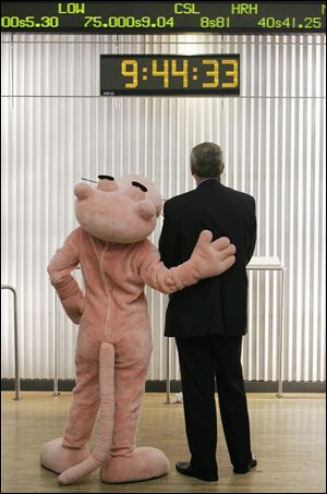 David Brown, president and CEO of Owens Corning, and the Pink Panther watched a stock ticker on the floor of the New York Stock Exchange on Nov. 11, 2006, after the building-materials maker, just out of Chapter 11 bankruptcy, began trading again on the exchange after a four-year absence.