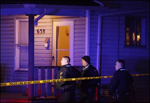 Police on the scene where a woman was shot at 658 Spring Street, today, in Toledo, Ohio.