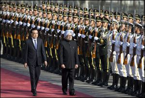 Indian Prime Minister Manmohan Singh, right, is accompanied by Chinese Premier Li Keqiang, left, as they inspect an honor guard during a welcome ceremony outside the Great Hall of the People in Beijing, China, today.