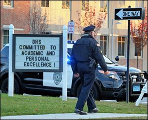 Danvers police are seen Wednesday, Oct. 23, 2013 at the Danvers High School, investigating a report of a sudden death inside the school in Danvers, Mass.