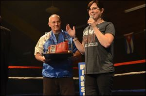 Harry Cummins, Executive Director of IBC, hands boxing gloves to Jodi Szczublewski of Clear Channel, as a thank you for their sponsorship and participation.