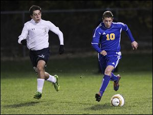 Findlay sophomore Justin Allsop (10) dribbles the ball as St. John's junior Mario Franco-DiTore (12) chases.