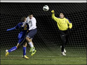 St. John's junior goal keeper Jarret Karalfa (1) punches the ball away from the goal as St. John's junior Mario Franco-DiTore (12), right, blocks Findlay junior Kyle Burns (12).