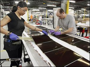Employees work on solar panels at the Xunlight Corp. plant.  A Xunlight official says the company 'got ahead of itself.'