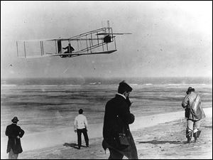 In this undated file photo, Orville and Wilbur Wright test their airplane on a North Carolina beach.