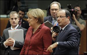 German Chancellor Angela Merkel, second left, and French President Francois Hollande, second right, arrive for a round table meeting at an EU summit today in Brussels.