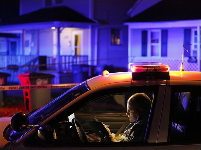 n6homicide-2 A Toledo police officer records information at the scene of a slaying in North Toledo on Wednesday night. Detectives have sworn out an arrest warrant for a man they believe is a suspect in the fatal shooting in the 600 block of Spring Street.