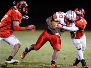 Bowsher player Khane Collins (20) is tackled by Rogers players Kameron Jones (2) and Mike Moore (4).